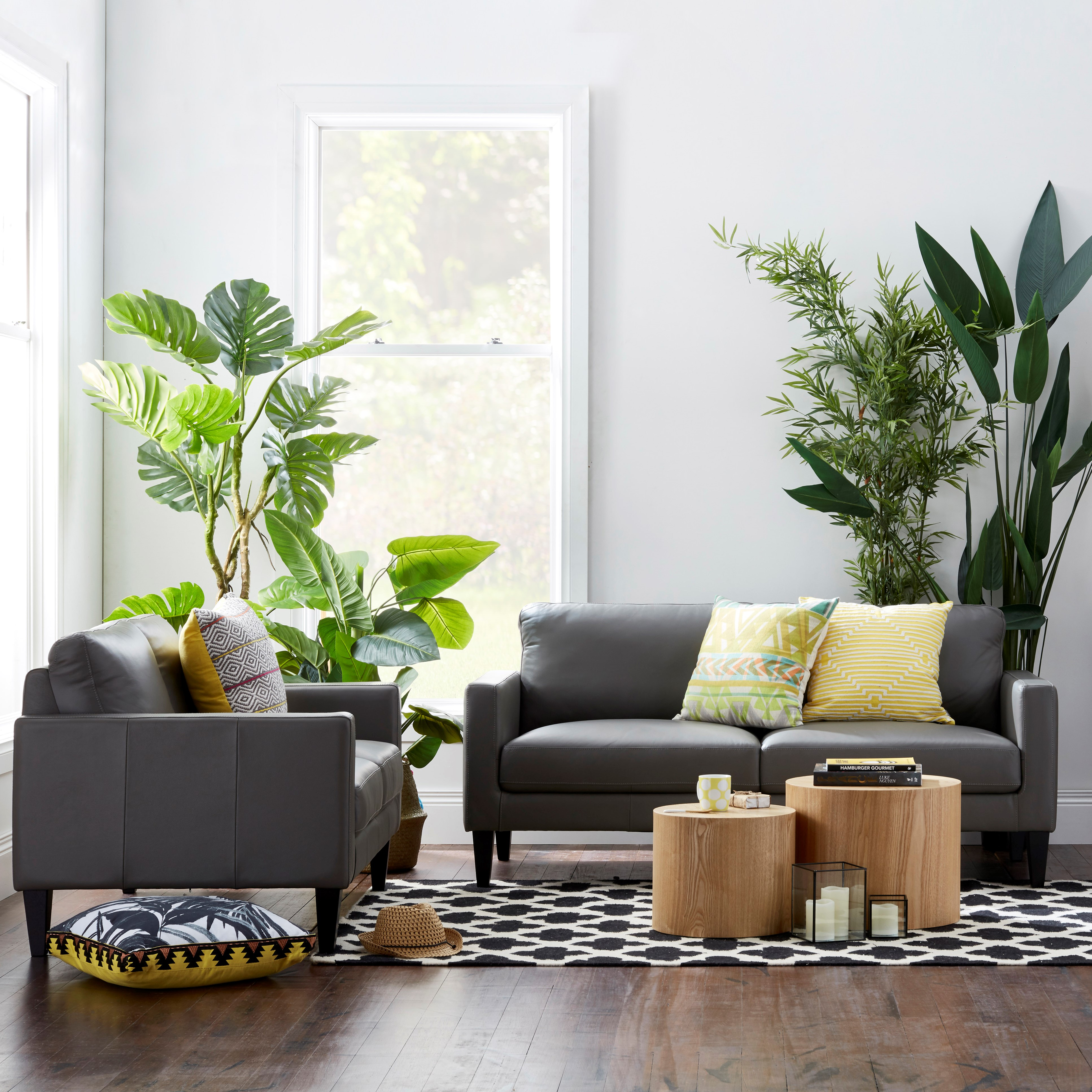 A living room with an armchair, a small couch and a small table in the center